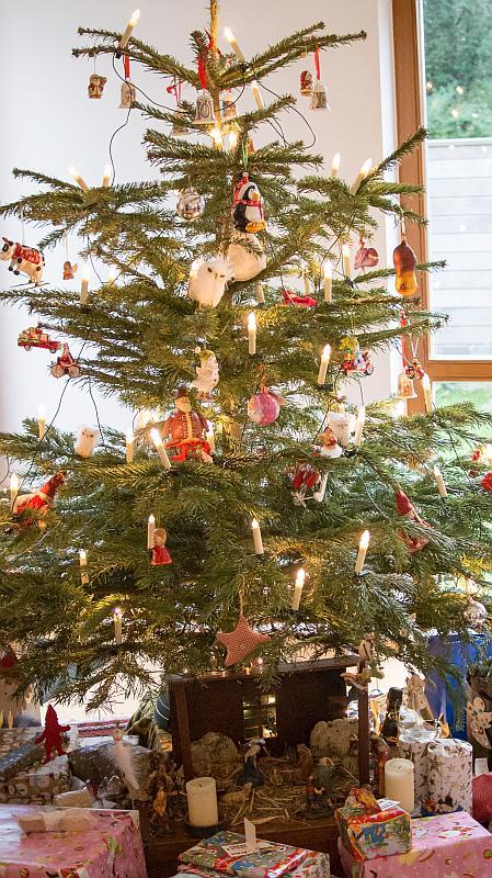 geschmückter Tannenbaum mit Geschenken und einer Krippe