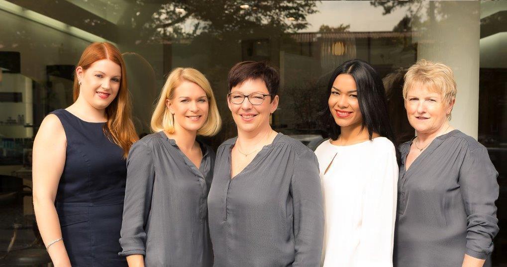 Teamfoto der Mitarbeiterinnen vor dem Schaufenster des Salons