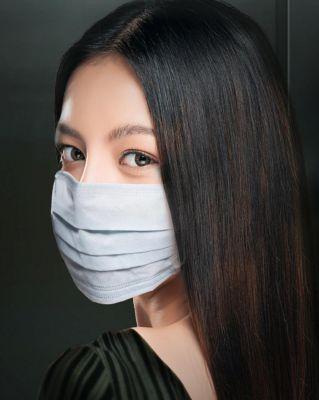 Eine Frau mit medizinischer Atemschutzmaske schaut über die Schulter.