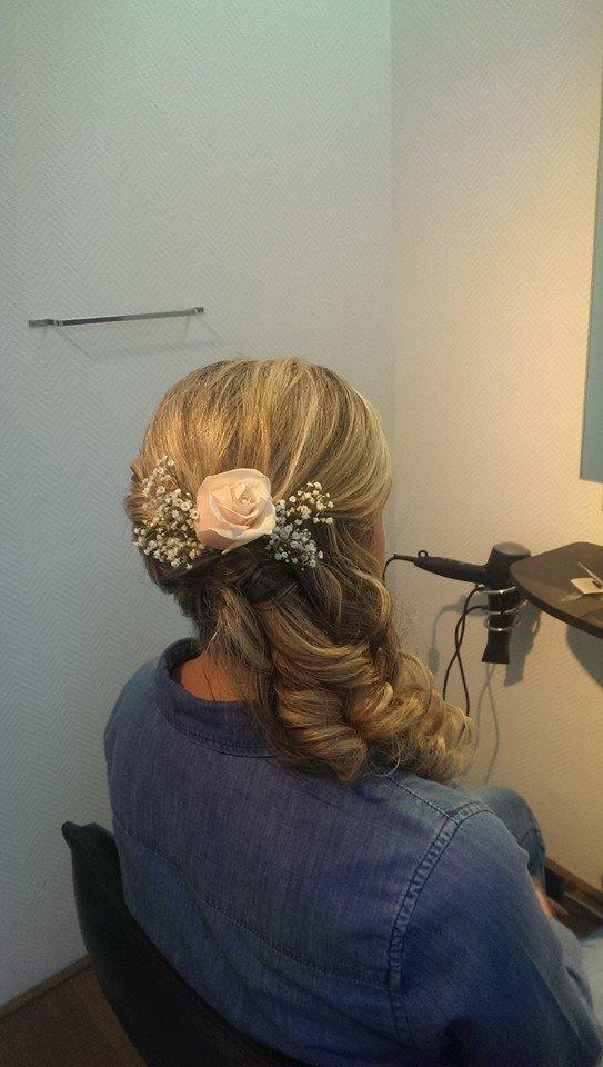 Eine Frau mit langen blonen Haaren hat eine neue Frisur für die Hochzeit bekommen, mit Rosengesteck