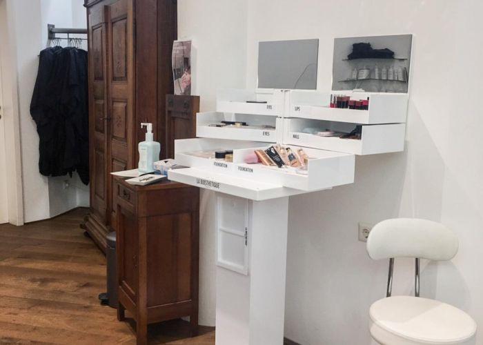 Ein weißes schränkchen mit Kasmetikartikel und Spiegeln.