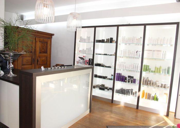 Empfangstheke und ein Schrank. Rechts ein helles Regal mit Shampoos und Pflegeprodukten.