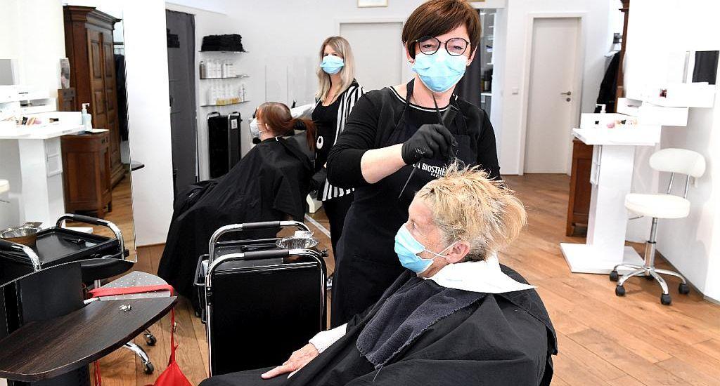 Foto im Salon. Die Friseurinnen kümmern sich mit Mundschutz um die Kundinnen.