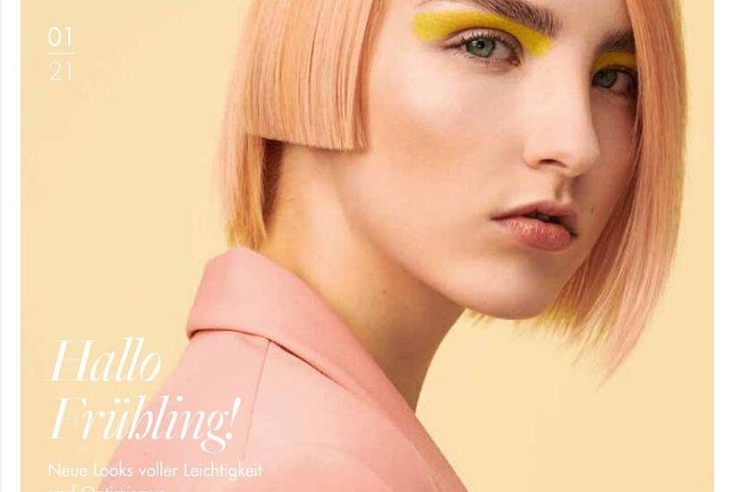 Titelseite der Zeitschrift, in hellen gelborange Farbtönen gehalten. Eine Frau mit kinnlangem Haarschnitt schaut über die Schulter in die Kamera.