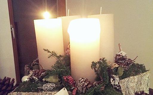 Adventskranz auf einem Stein mit großen weißen Kerzen, zwei brennen